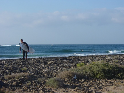 Surfer on the rocky beach at Majanichio inside, Fuerteventura.